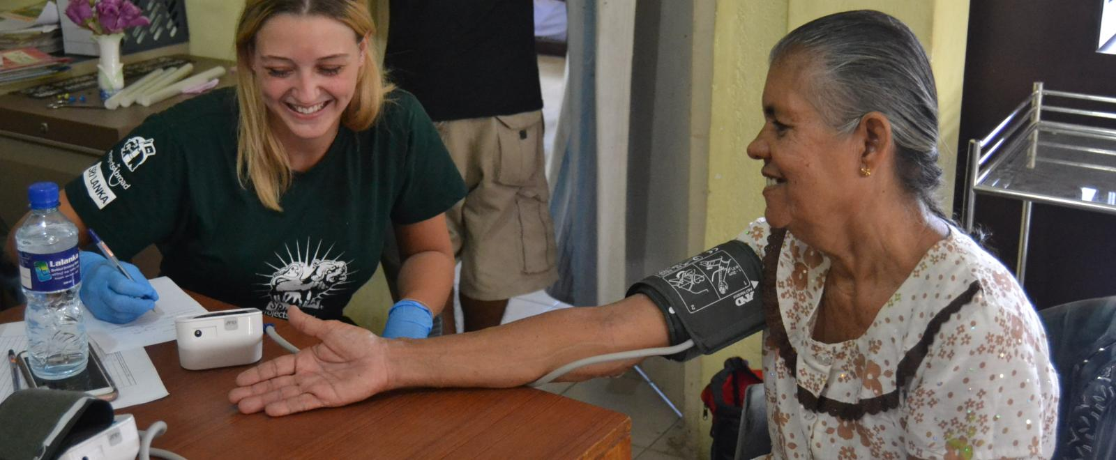 A student doing a medical internship for high school students in Sri Lanka checks blood pressure levels for a local woman.